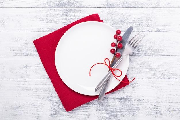 Mesa navideña con plato blanco vacío y cubiertos