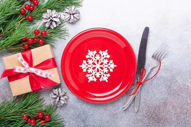 Mesa navideña con plato blanco vacío, presente y cubiertos