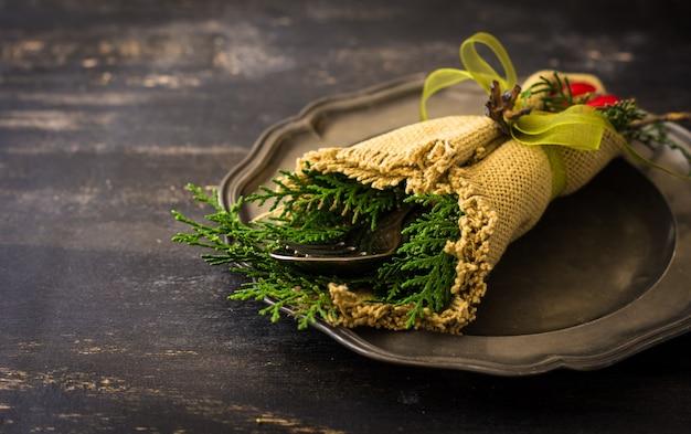 Mesa navideña con plato de cerámica y cubiertos en mesa de madera