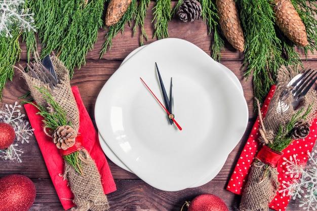 Mesa navideña con plato, cubiertos y decoraciones.
