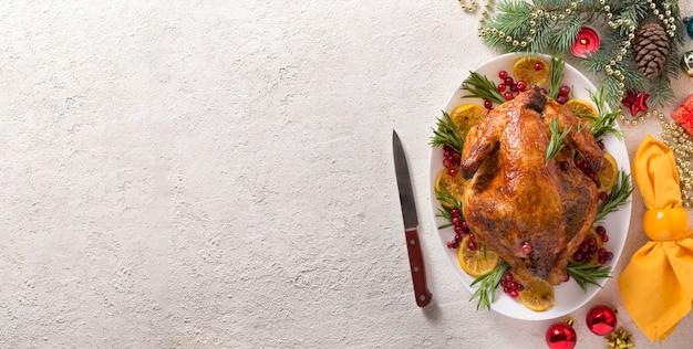 La mesa navideña con pollo al horno está decorada festivamente con velas.