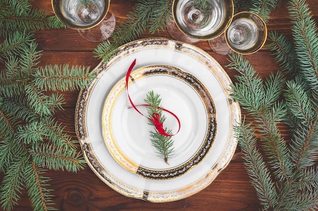 Mesa navideña con ramas de pino y decoraciones vista superior