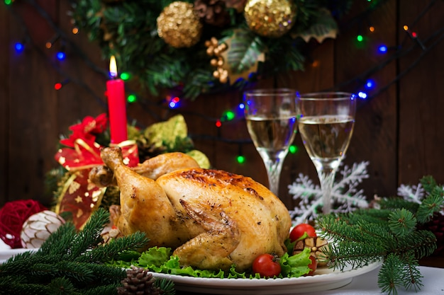 Mesa navideña servida con pavo, decorada con brillantes guirnaldas y velas.