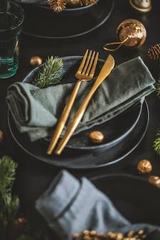 Mesa navideña servida en tonos oscuros con decoración dorada.