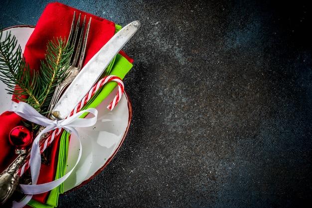 Mesa navideña con tenedor, cuchillo y adornos navideños