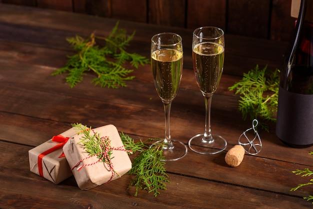 Mesa navideña con vasos y una botella y regalos