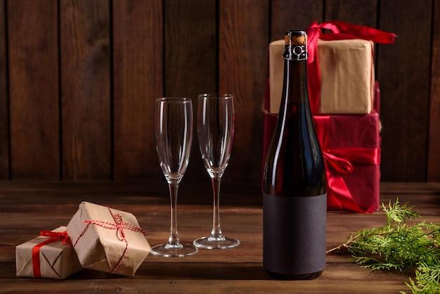 Mesa navideña con vasos y una botella de vino
