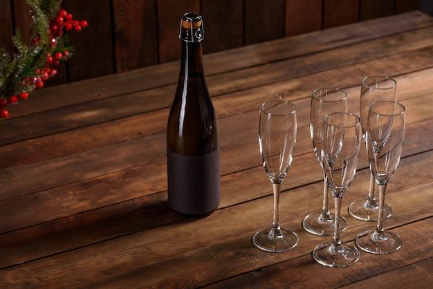 Mesa navideña con vasos y una botella