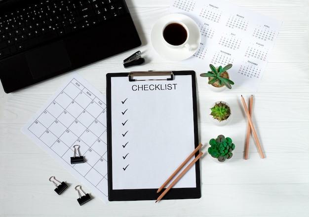 Mesa de negocios de escritorio de oficina con ordenador portátil, lista de verificación de papel en blanco, calendario, anteojos, taza de café y plantas verdes sobre fondo blanco de madera. vista superior y plano