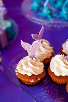 Mesa para niños con cupcakes con cobertura blanca decorada con cola de sirena morada.