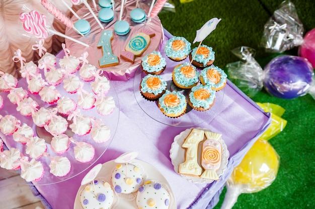 Mesa para niños con cupcakes con tapa azul y naranja y elementos decorativos en colores rosa y azul brillante.