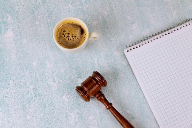Mesa de oficina con accesorios planos en una libreta espiral una taza de café, jueces martillo