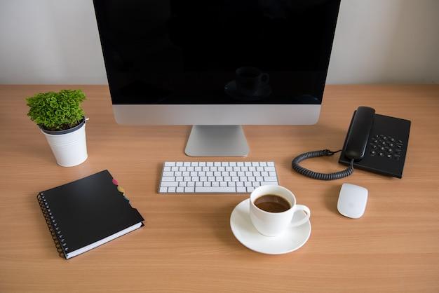 Mesa de oficina con computadora personal, cuaderno, teléfono, teclado, mouse, taza de café y maceta