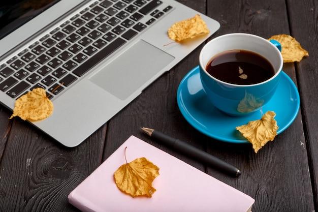 Mesa de oficina con cuaderno en blanco y portátil / taza de café