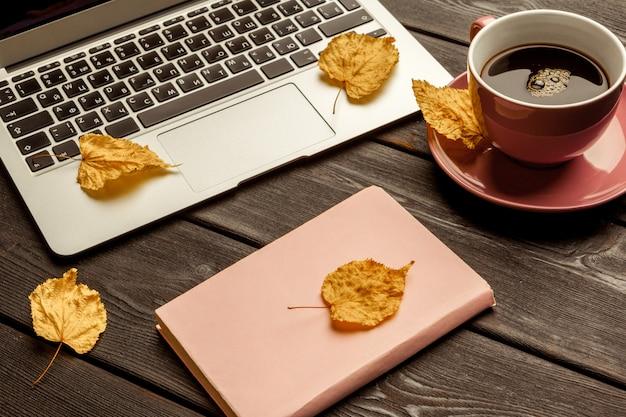Mesa de oficina con cuaderno en blanco y portátil