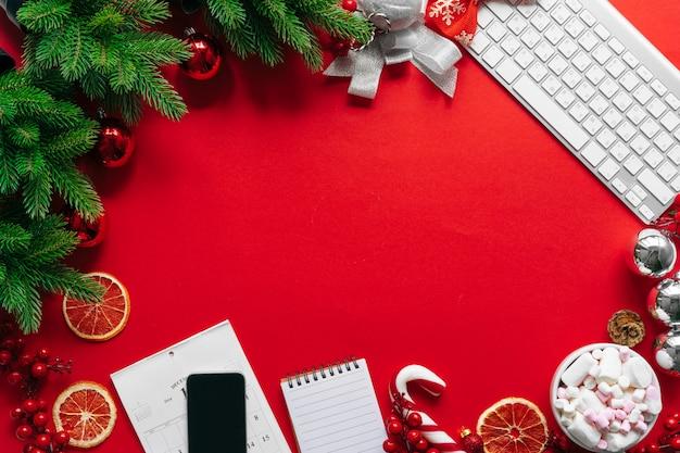 Mesa de oficina con dispositivos, suministros y decoración navideña.