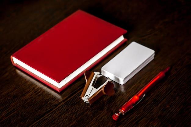 Mesa de oficina con libreta, lápices de colores, suministros y tarjetas de visita.