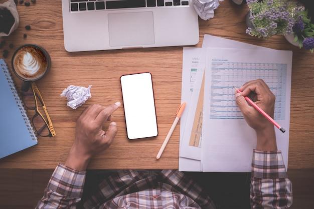 Mesa de oficina de madera con papel de informe de control empresario, pantalla en blanco en el móvil