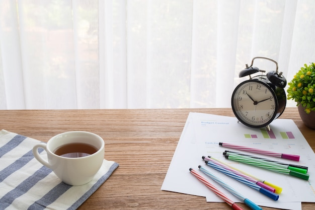 Mesa de oficina de madera con taza de bebida caliente
