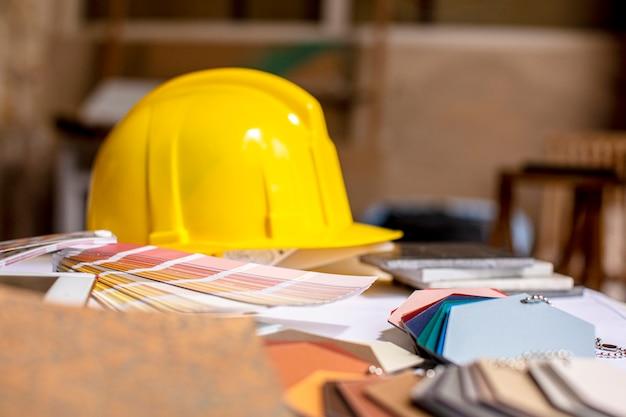 Mesa de oficina con muestras de material y casco de construcción.