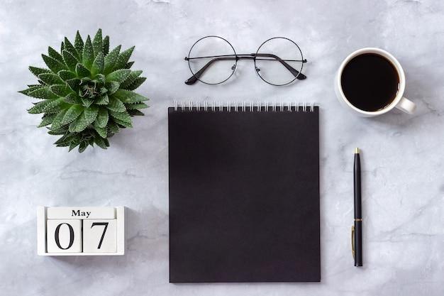 Mesa de oficina o local, calendario 7 de mayo. bloc de notas, café, suculentas, gafas concepto lugar de trabajo con estilo