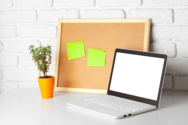 Mesa de oficina con ordenador portátil y tablón de anuncios. detalles del negocio interior