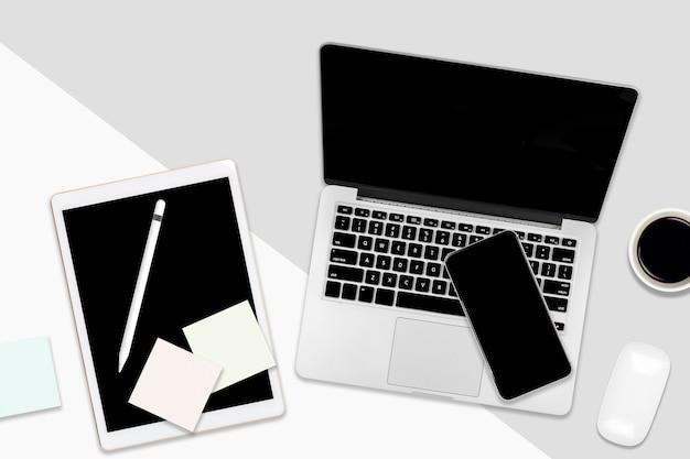 Mesa de oficina plana con ordenador portátil, tableta digital, teléfono móvil y accesorios.
