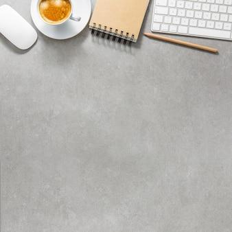 Mesa de oficina con taza de café, teclado y bloc de notas