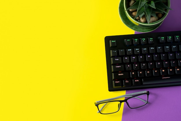 Mesa de oficina con vidrios, planta y teclado. fondo con copyspace