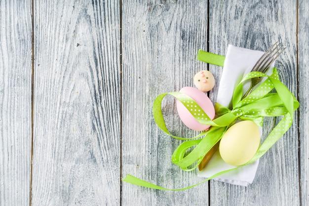 Mesa de pascua con huevos, cinta y cubiertos