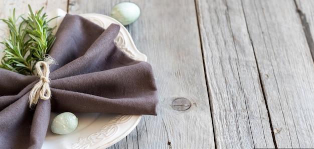 Mesa de pascua con huevos y romero en la mesa de madera gris de cerca con espacio de copia