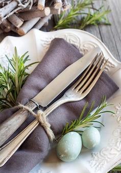 Mesa de pascua con huevos y romero en la mesa de madera gris de cerca