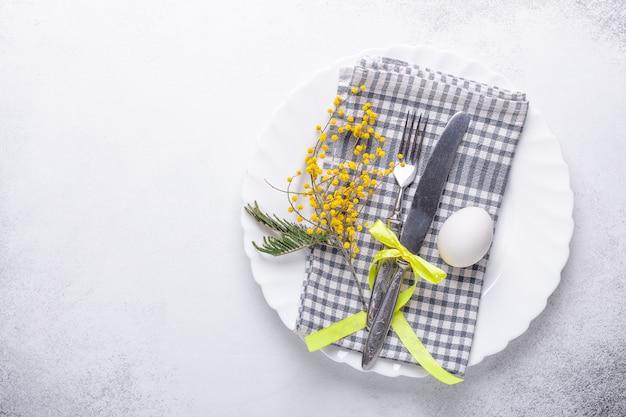 Mesa de pascua. plato blanco, flores de mimosa y cubiertos sobre fondo de piedra