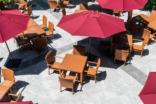 Mesa de patio exterior vacía y silla con sombrilla