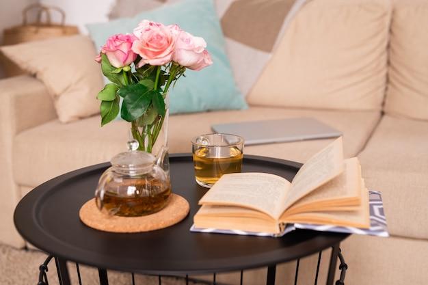 Mesa pequeña con ramo de rosas en un vaso de agua, té verde en tetera y taza y libro abierto de historias contra el sofá con almohadas y tableta