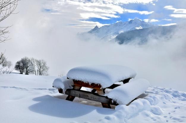 Mesa de picnic nevada en paisaje natural