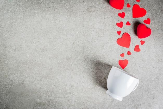 Mesa de piedra gris con una taza de café, decorada con papel y corazones rojos de felpa