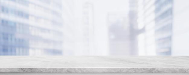 Mesa de piedra de mármol blanco vacío y borroso edificio de pared de ventana de vidrio