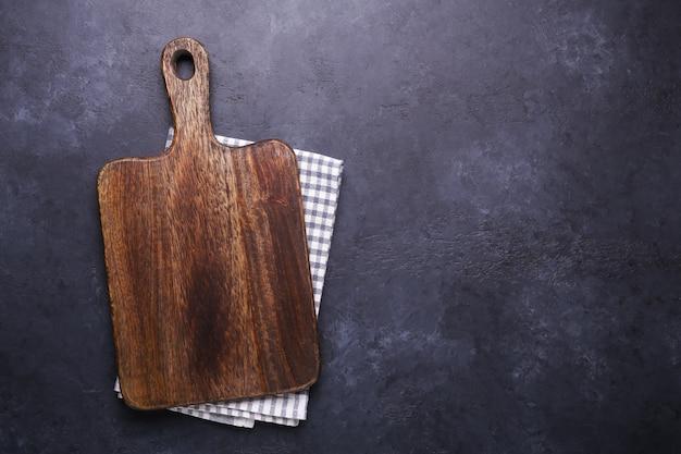 Mesa de piedra oscura con tabla de cortar y servilleta de lino. espacio de copia