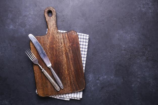 Mesa de piedra oscura con tabla para cortar y servilleta de lino. tenedor y cuchillo vintage. espacio de copia.