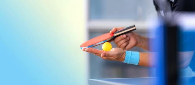 Mesa de ping pong, hombre jugando tenis de mesa con raqueta y pelota en un pabellón deportivo