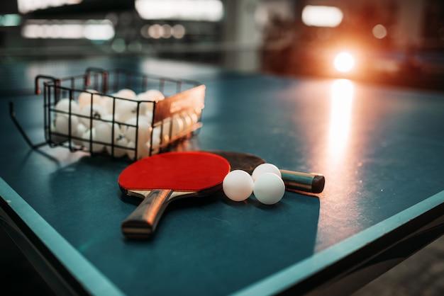 Mesa de ping pong, raquetas y pelotas en un polideportivo