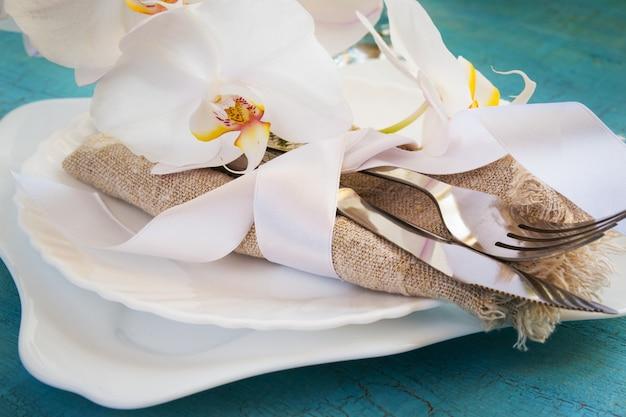 Mesa de primavera con decoraciones de orquídeas blancas y servilletas.