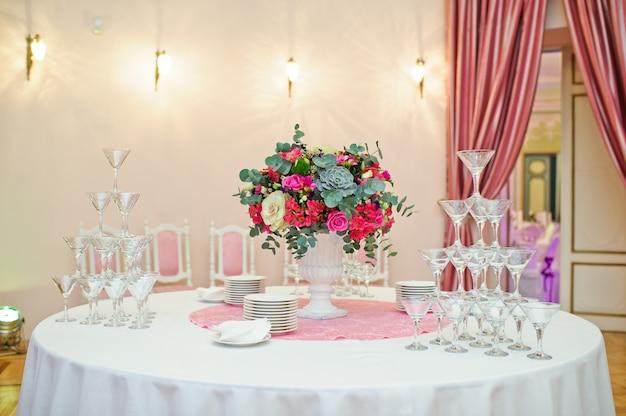 Mesa puesta en el banquete de bodas en el restaurante, estilo clásico con manteles y servilletas blancas, jarrones con flores.
