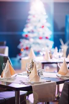 Mesa puesta en el restaurante con árbol de navidad