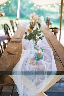 Mesa de recepción para bodas o cenas, decorada en estilo rústico.