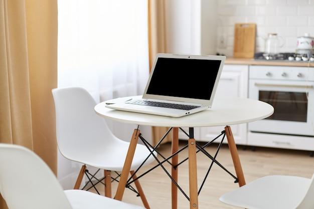 Mesa redonda blanca con computadora portátil con pantalla en blanco para publicidad y teléfono inteligente, espacio de trabajo para autónomos en casa en la cocina luminosa cerca de la ventana.