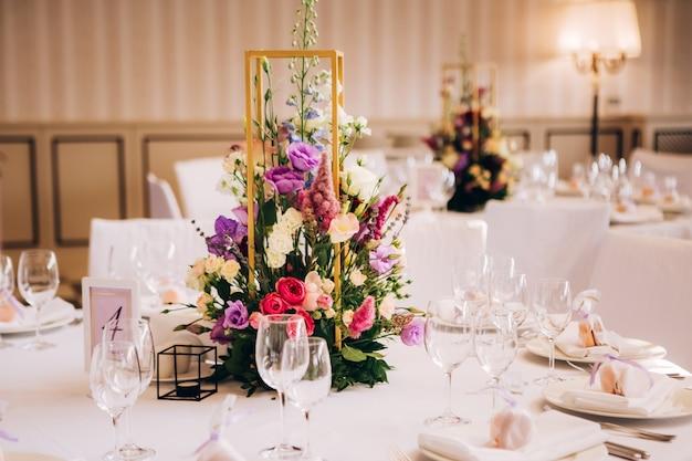 Mesa redonda blanca con flores naturales.