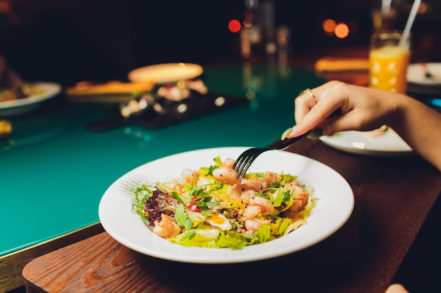 Mesa de restaurante o cafetería con plato de ensaladas y vino. dos personas hablando sobre fondo. imagen entonada