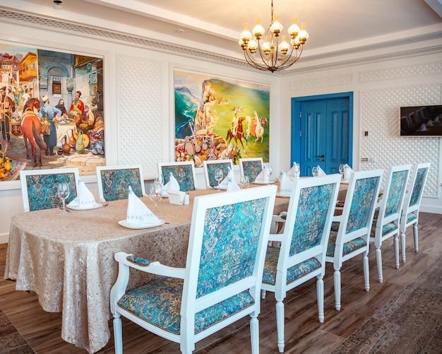 Mesa de restaurante con sillas clásicas blancas y tela turquesa.